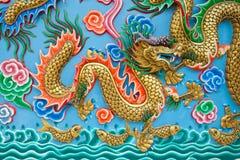 在蓝色墙壁上的金黄龙雕象 免版税图库摄影