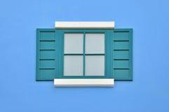 在蓝色墙壁上的绿色木窗口 免版税图库摄影