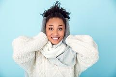 在蓝色墙壁演播室冬天概念盖子耳朵隔绝的年轻非洲妇女 免版税库存照片