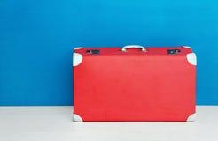 在蓝色墙壁的红色减速火箭的手提箱 旅行和冒险 库存图片