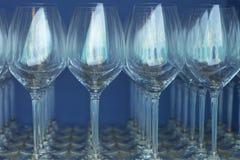 在蓝色墙壁的背景的酒杯 库存图片
