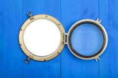 在蓝色墙壁的黄铜舷窗,打开,与裁减路线 免版税库存照片