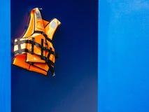 在蓝色墙壁背景安全设备抢救的救生背心 图库摄影