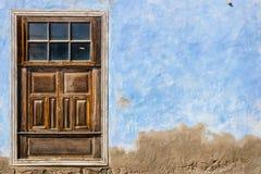 在蓝色墙壁背景的布朗门 免版税库存图片