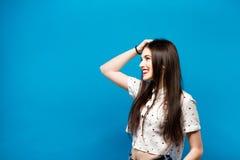 在蓝色墙壁背景隔绝的想法的少妇画象 空白衬衣 图库摄影