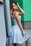 在蓝色夏天礼服的美好的白肤金发的年轻时装模特儿,肉欲摆在绿色墙壁旁边 库存照片