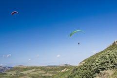在蓝色多云天空的滑翔伞 免版税图库摄影