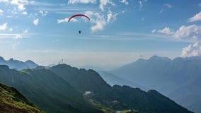 在蓝色多云天空的红色滑翔伞在绿色山 与下面下来电车的绿色山谷 Krasnaya Polyana,索契 免版税库存图片