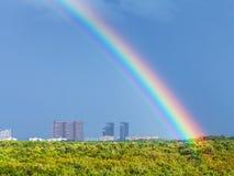 在蓝色多雨天空的彩虹在城市和都市公园 库存图片