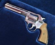 在蓝色天鹅绒背景的左轮手枪大酒瓶357 免版税库存照片