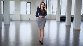 在蓝色女衬衫、灰色裙子和高跟鞋打扮的美丽的长发女商人在办公室走 影视素材