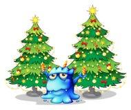 在蓝色妖怪的后面的巨型圣诞树 免版税库存图片