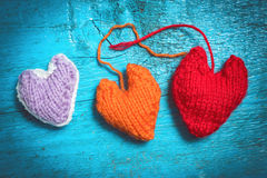 在蓝色委员会的五颜六色的被编织的心脏 免版税库存图片