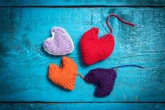 在蓝色委员会的五颜六色的被编织的心脏 免版税图库摄影