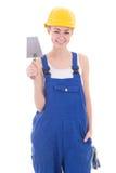 在蓝色工作服的年轻美丽的妇女建造者有修平刀isol的 库存照片