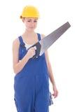 在蓝色工作服的年轻美丽的妇女建造者有手工锯的 免版税库存图片