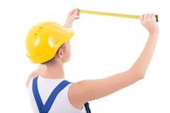 在蓝色工作服的年轻美丽的妇女建造者有措施轻拍的 库存照片