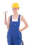 在蓝色工作服的年轻美丽的妇女建造者有锤子isol的 免版税库存照片