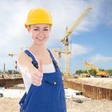 在蓝色工作服赞许的美丽的妇女建造者 免版税库存照片