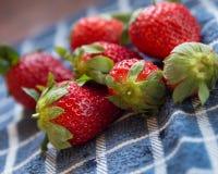 在蓝色布料的红色成熟甜草莓 免版税库存照片