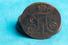 在蓝色布料背景有17世纪的一枚老俄国硬币,所有细节是可看见的 库存图片