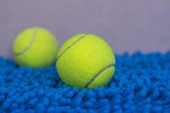 在蓝色席子的网球 免版税库存图片