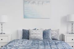在蓝色床上的海报与枕头在白色简单的卧室内部与在内阁的灯 实际照片 免版税库存图片