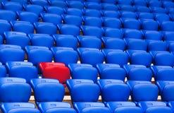 在蓝色扶手椅子背景的红色扶手椅子  是空白不同的磁盘 是 库存照片