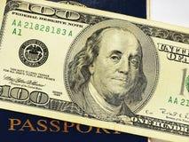 在蓝色护照关闭的一百元钞票 库存照片