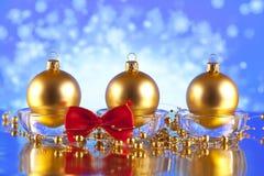 在蓝色抽象背景的三个圣诞节球 库存照片