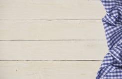 在蓝色方格的桌布的土气木背景 免版税库存照片
