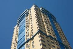 在蓝色无云的天空垂直视图的高黄色现代大厦 库存照片