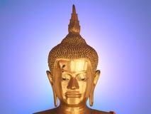 在蓝色明亮的背景的菩萨雕象面孔 库存照片