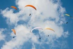 在蓝色晴朗的天空的滑翔伞 小组滑翔伞在夏天晴天飞行在喀尔巴汗 免版税图库摄影