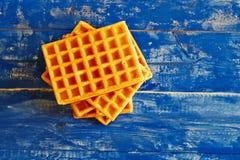 在蓝色木台式的金黄奶蛋烘饼 库存图片