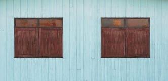 在蓝色木墙壁上的老木窗口 图库摄影