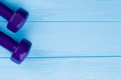 在蓝色木头的哑铃与拷贝空间 免版税图库摄影