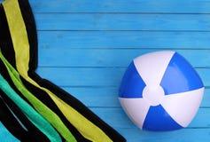 在蓝色木板条的镶边海滩毛巾和水球 库存图片