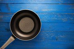 在蓝色木板条背景拷贝空间的厨房平底锅您的 免版税库存照片
