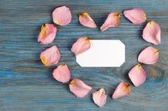 在蓝色木板的桃红色玫瑰花瓣想象心脏形状有里面空白的白色卡片的 库存图片