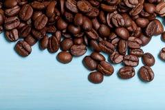 在蓝色木桌上的咖啡豆 免版税图库摄影