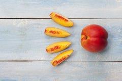 在蓝色木桌上的新鲜的切的油桃 图库摄影