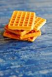 在蓝色木桌上的金黄奶蛋烘饼 免版税库存照片