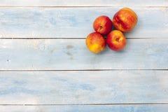 在蓝色木桌,顶视图上的新鲜的油桃 免版税库存照片