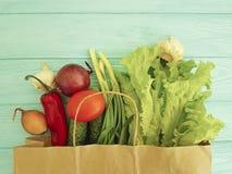 在蓝色木纸袋维生素的有机菜 免版税图库摄影