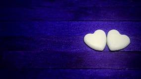 在蓝色木背景的两白色心脏 库存图片