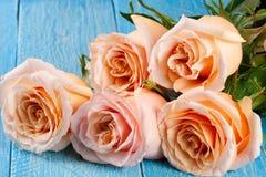 在蓝色木背景的五朵新鲜的米黄玫瑰 库存图片