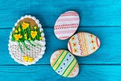 在蓝色木背景的五颜六色的复活节曲奇饼 免版税库存图片