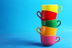在蓝色木背景的五颜六色的杯子 免版税库存照片
