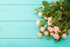 在蓝色木背景的五颜六色的玫瑰 免版税库存照片